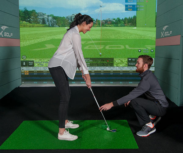 X-Golf Coach Giving Female Player Golf Lesson
