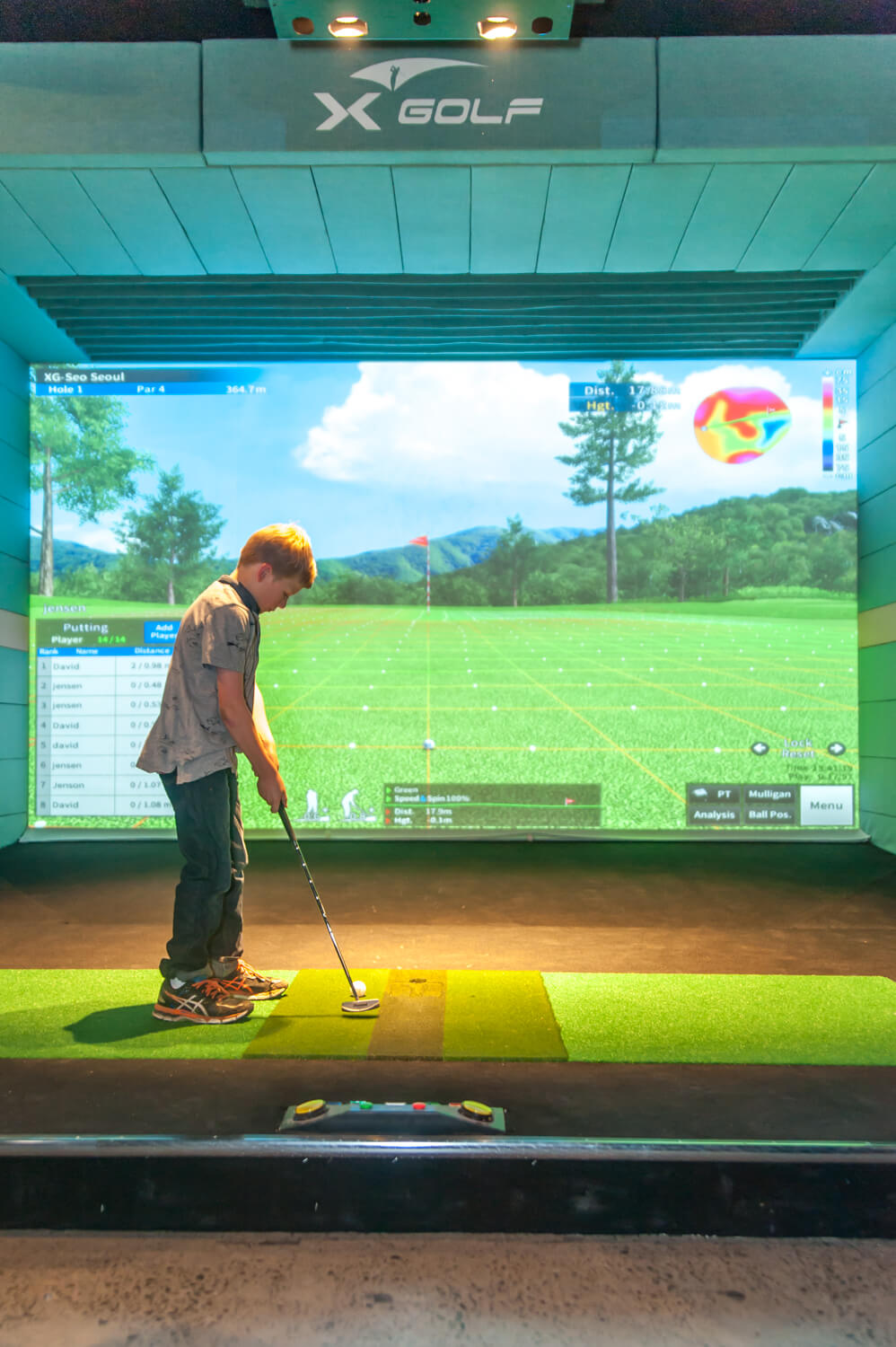 Boy playing X-Golf Simulator