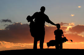 Father & Son walking Golf Course at Sunset