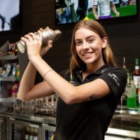 Girl standing in bar shaking a cocktails