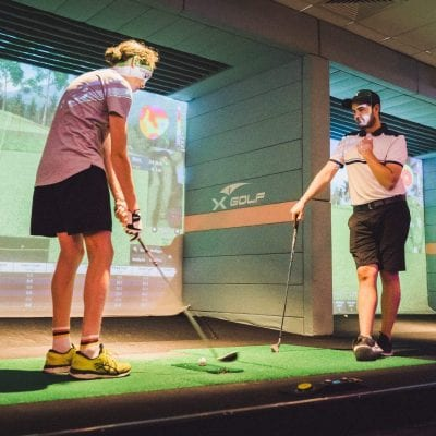 Man getting golf lesson on golf simulator XGolf Geelong