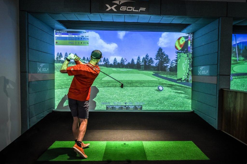 man hitting golf ball on x-golf simulator