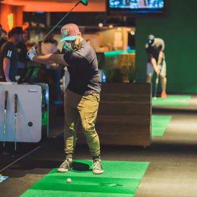 man hitting ball on golf simulator